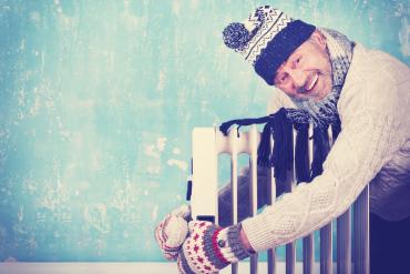 Mann umarmt Heizung in WintererkleidungMann umrmt Heizung in Wintererkleidung