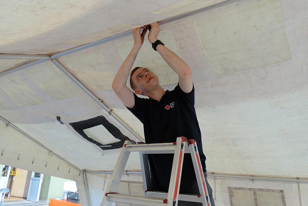 Alexander Sondern beim Verlaschen eines Zelts am Zeltgestänge