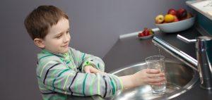 Kind füllt am Spülbecken Wasser in Wasserglas