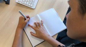 Linkshänder schreibt mit Block und Stift