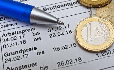 Stromrechnung mit Stift und Euromünzen