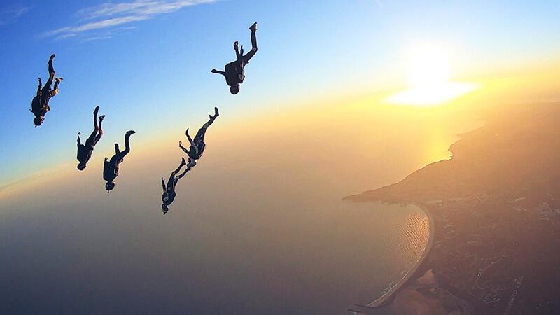 Fallschirmspringer in Formation vor Sonnenuntergang