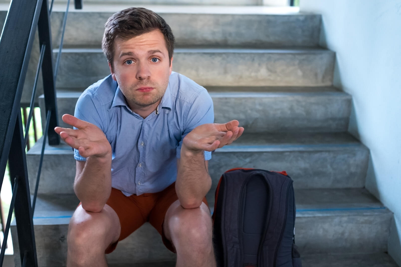 Mann (ausgesperrt) auf Treppe sitzend