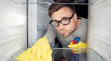 Kühlschrankreinigung: Mann reinigt Kühlschrank.