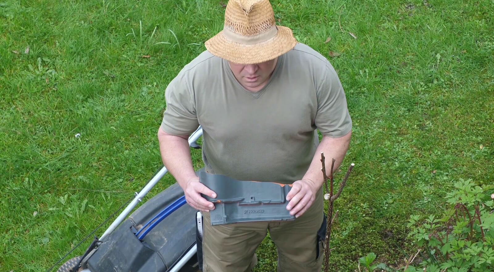 Mann im Garten mit kaputter Dachziegel
