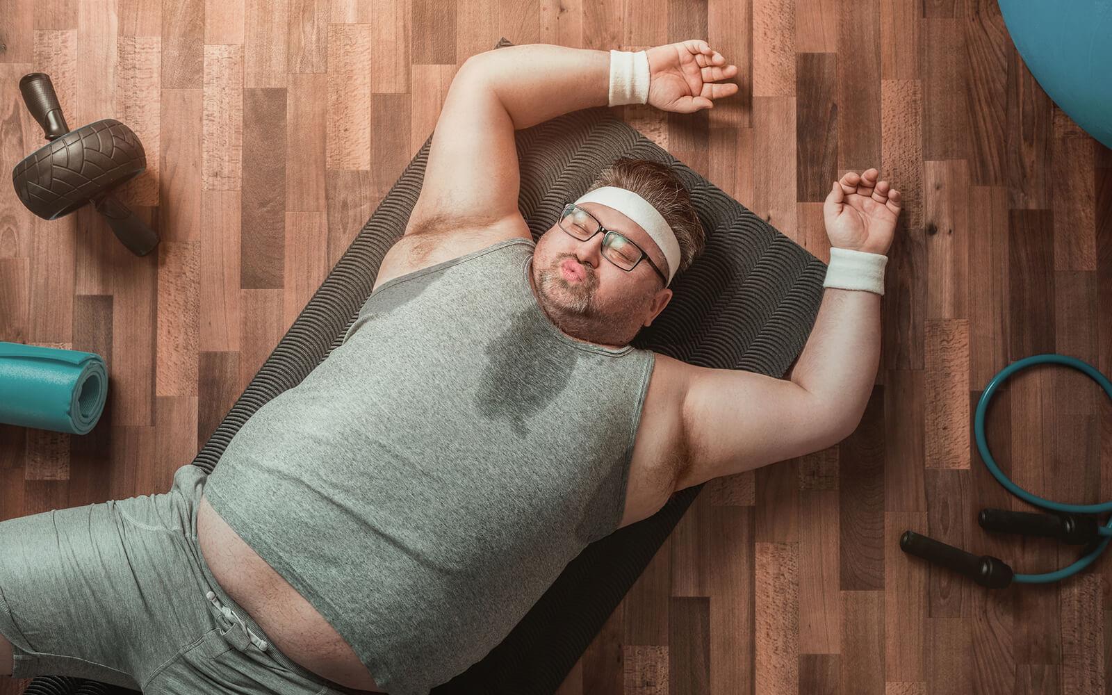 Mann im verschwitztem Hemd liegt auf Boden
