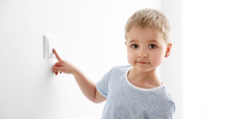 Kind drückt Lichtschalter