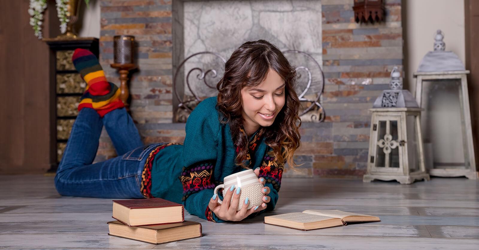 Frau liest auf Fußboden ein Buch