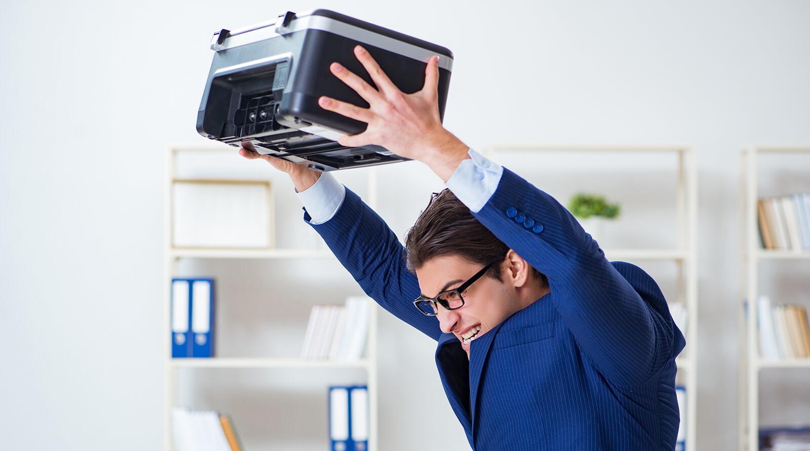 Mann mit Drucker in den Händen im Büro