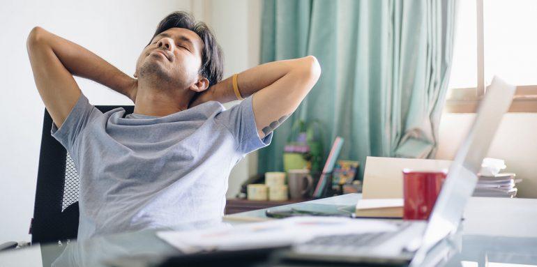 Mann entspannt am Schreibtisch im Homeoffice