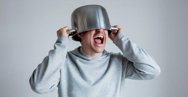 Mann mit Topf über seinem Kopf