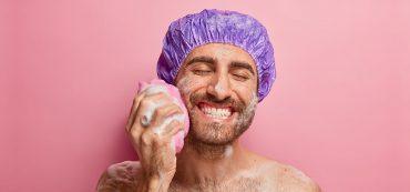 Duschender Mann mit Schwamm und Schaum