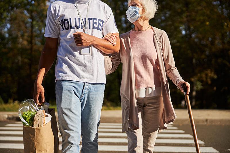 Junger Mann hilft Frau beim Einkaufen